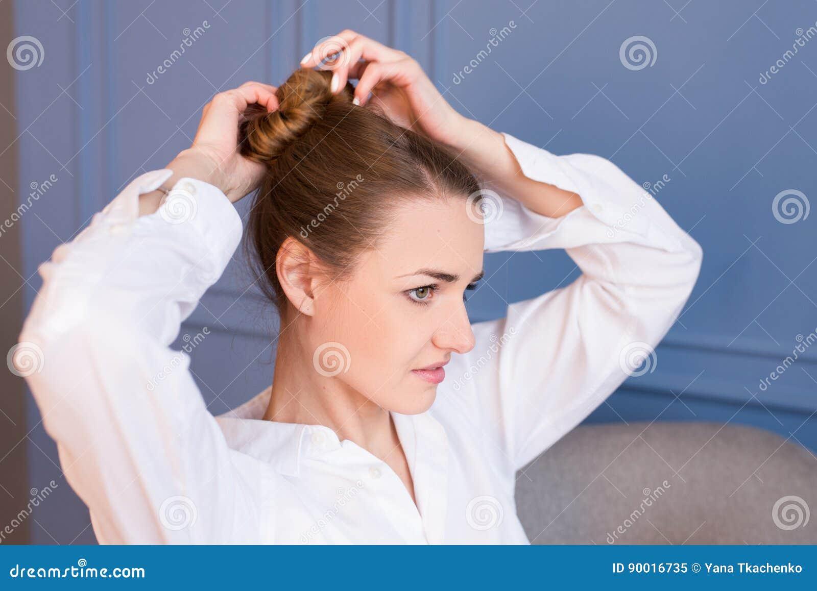 Jong mooi meisje die in wit men'soverhemd haar bruin haar in broodje maken