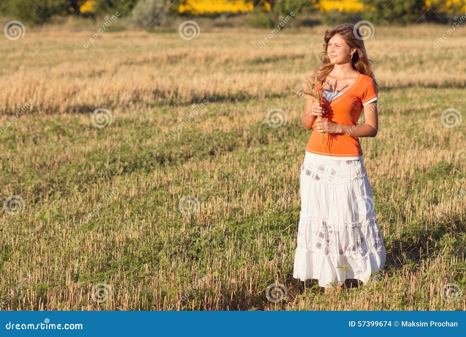 Jong mooi meisje op het gebied met oren in de hand