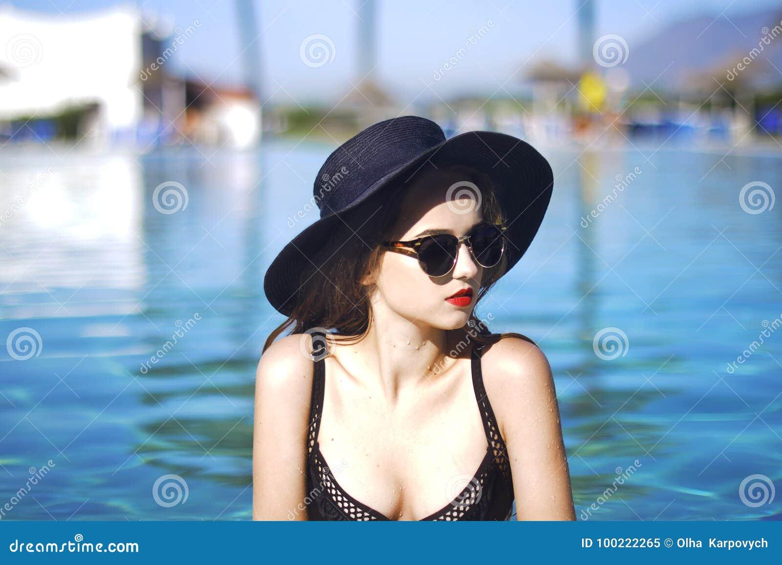 Jong mooi meisje in zwarte manierhoed, fluweelhuid, rode lippen, het zwarte zwempak stellen in de pool in blauw water, modieuze s