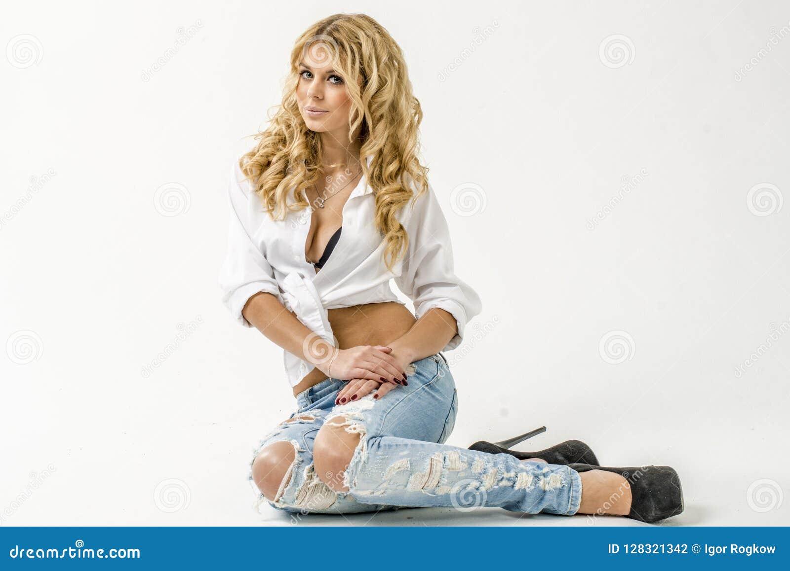 Jong mooi meisjesblonde in een wit overhemd en jeans met hiaten