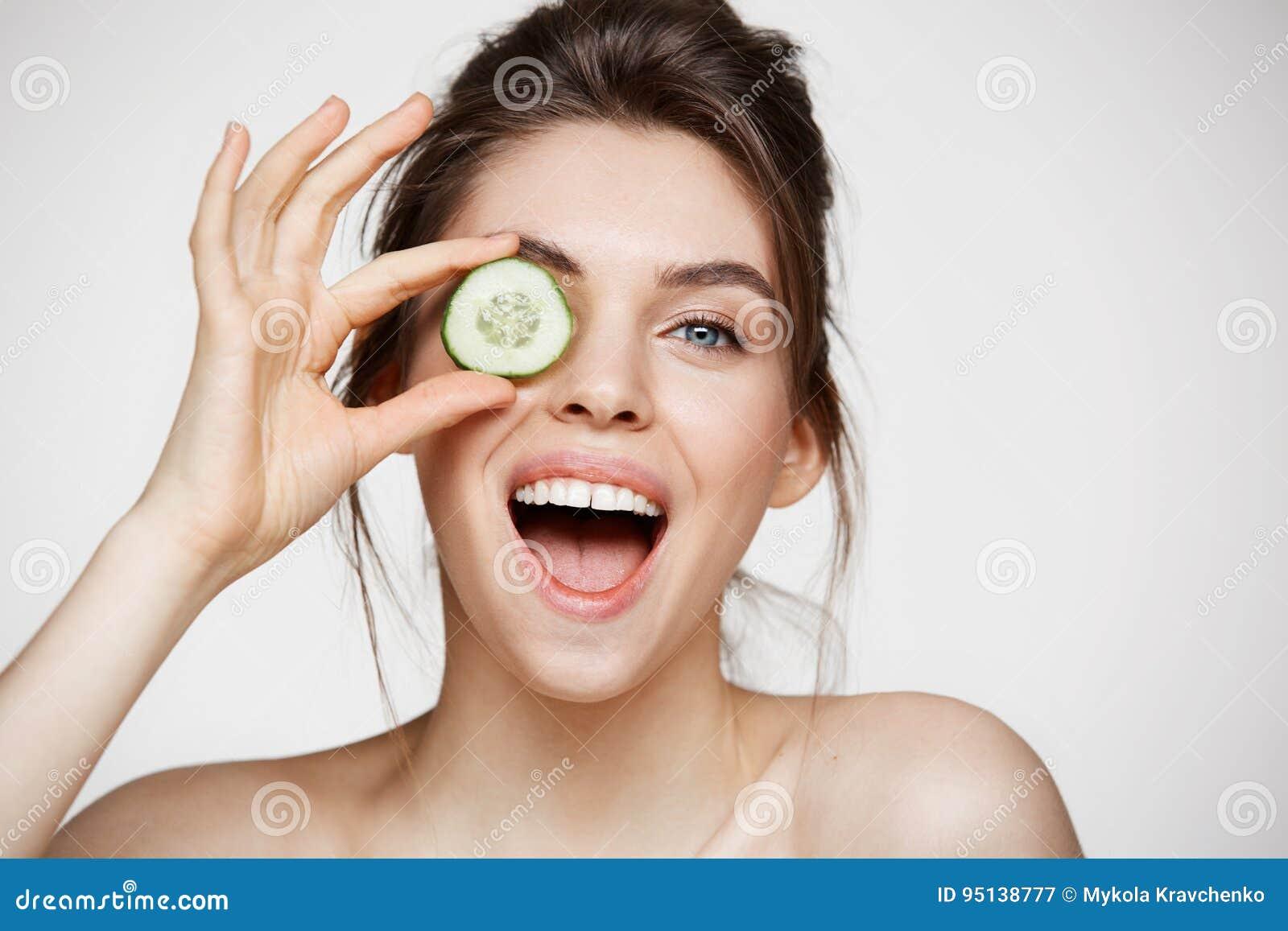Jong mooi naakt meisje het glimlachen verbergend oog achter komkommerplak die camera over witte achtergrond bekijken