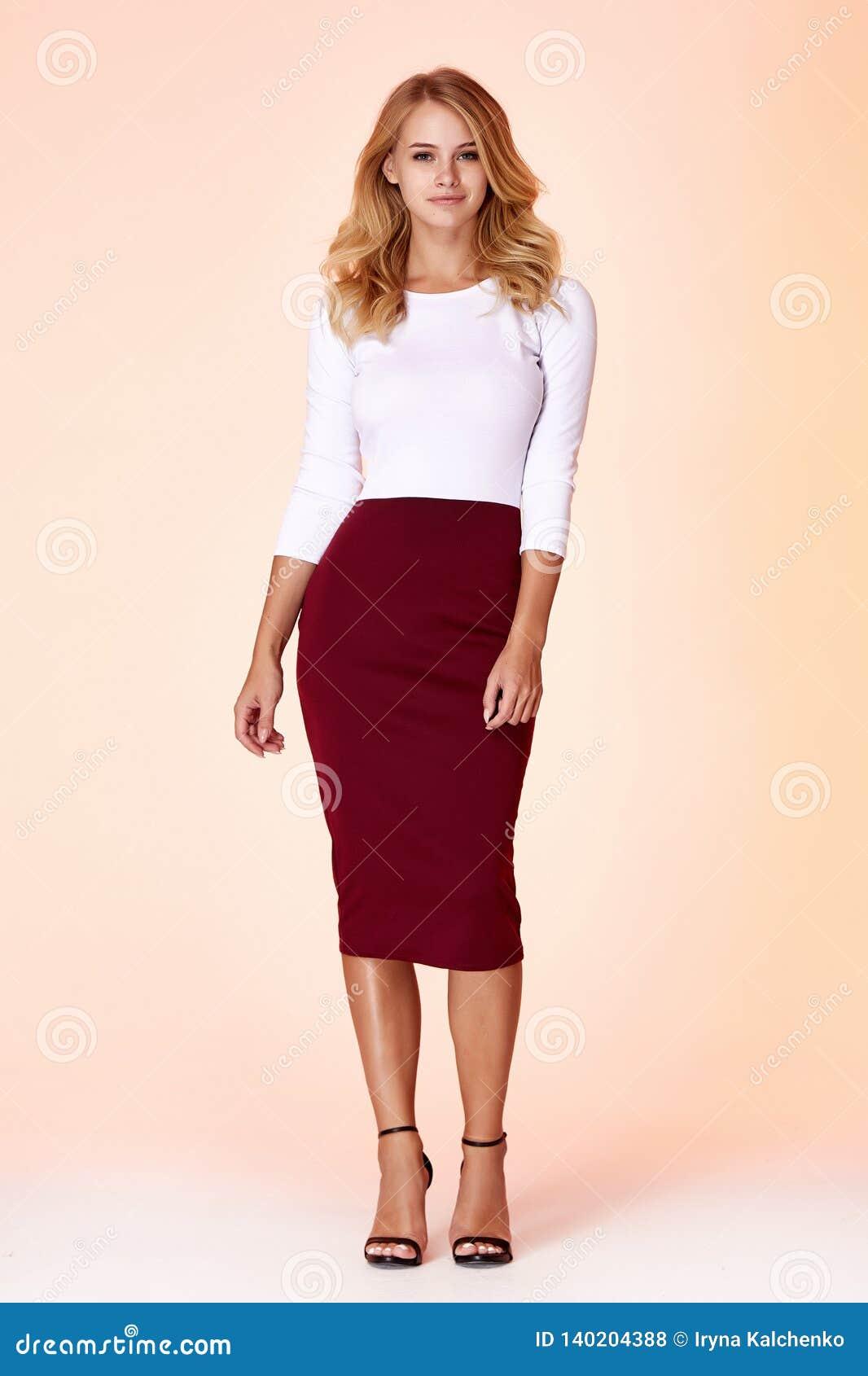 Jong mooi vrouwelijk model in de witte de kledings van de achtergrond blouse van de het haarmake-up van de magere rok studiovrouw