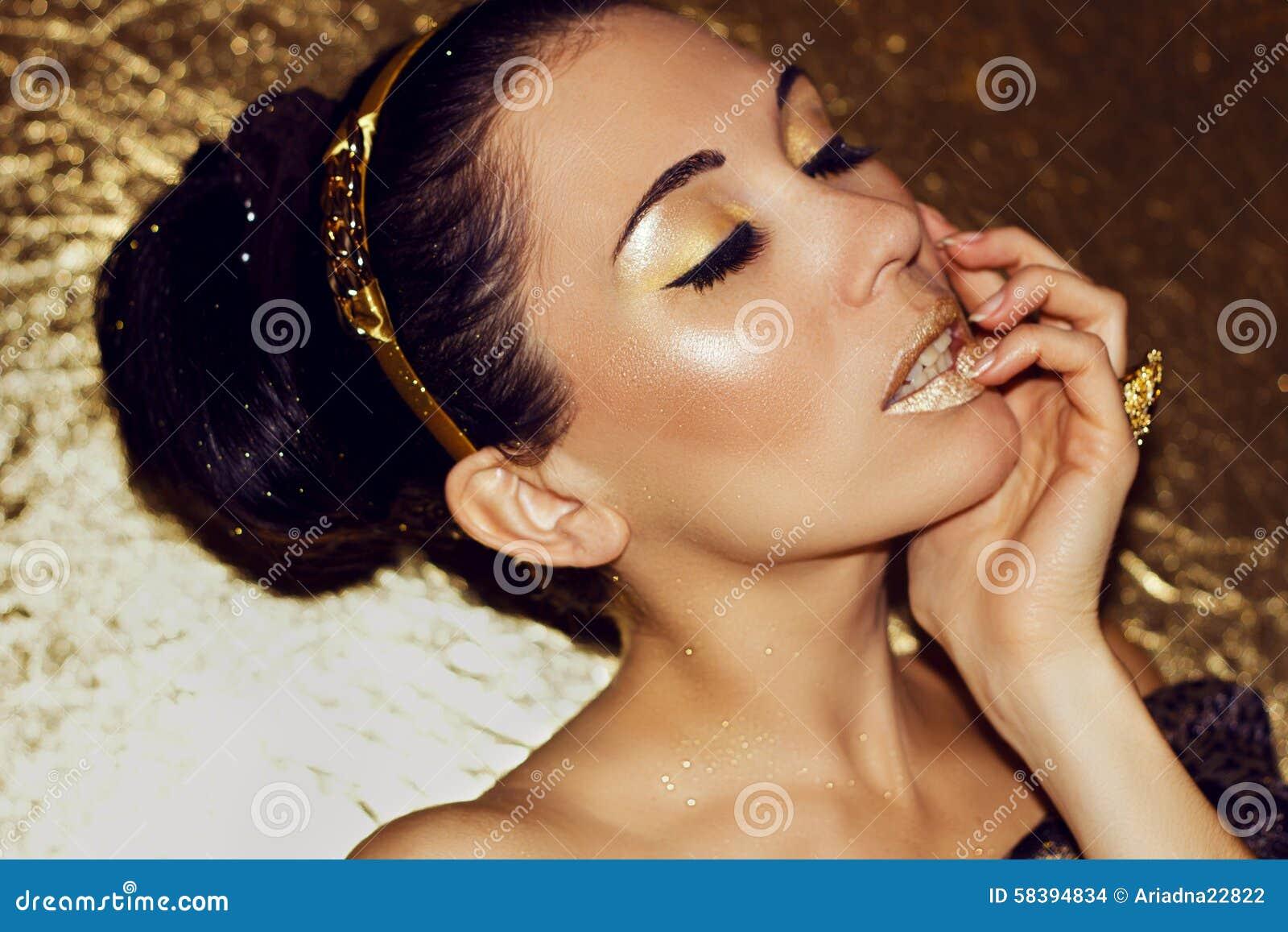 Jong mooi vrouwenbrunette met retro kapsel, hoepel Gouden samenstelling