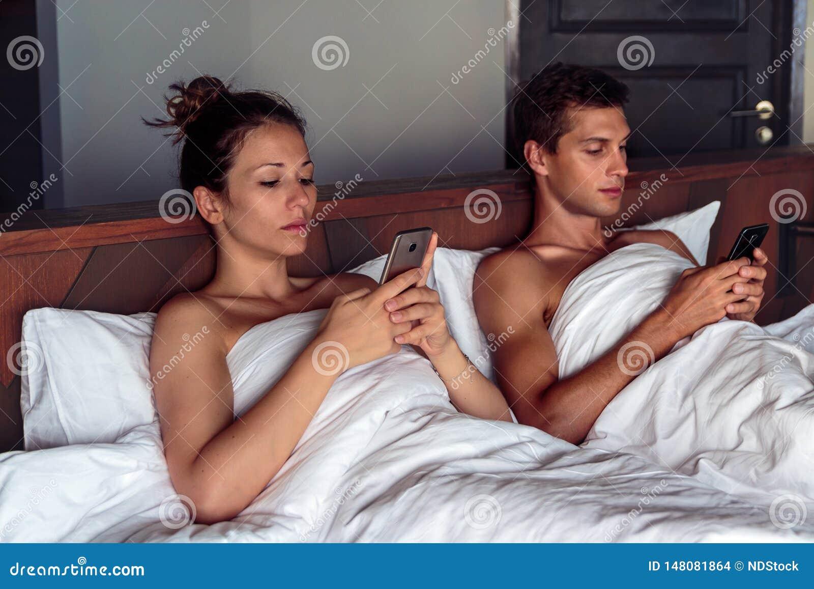 Jong paar in bed die hun smartphone gebruiken die elkaar negeren