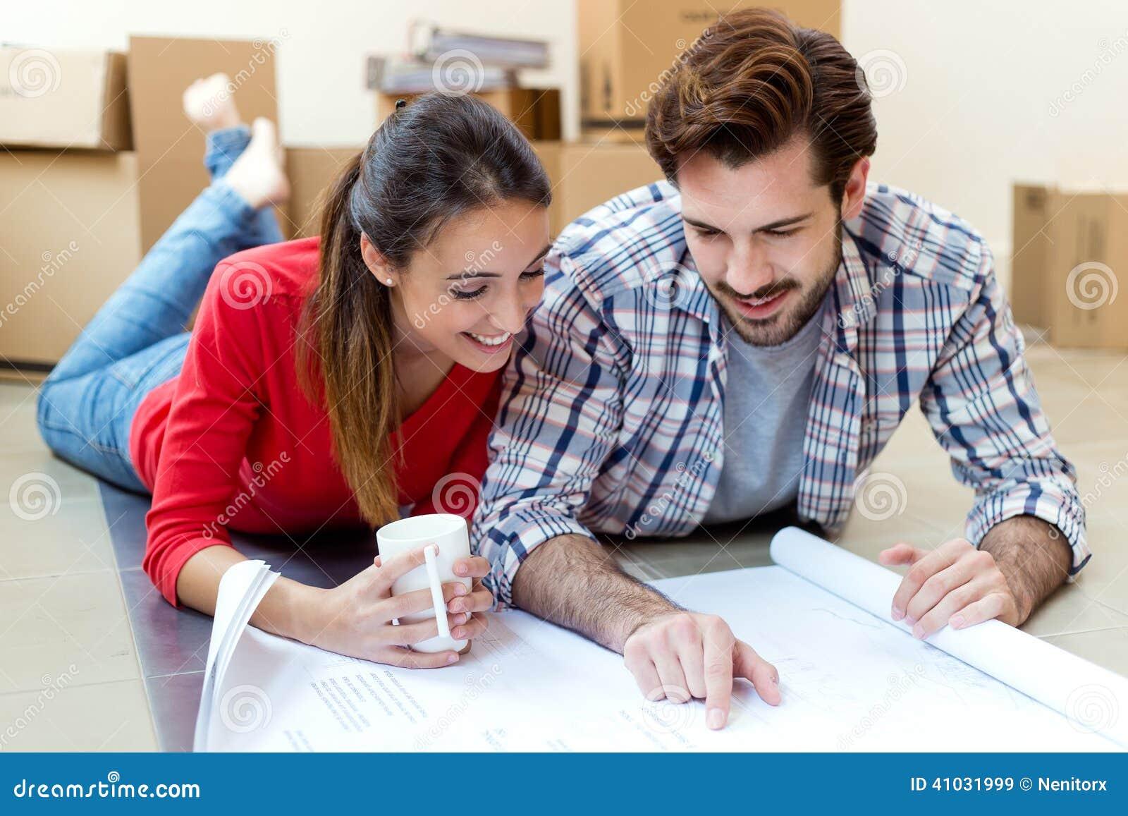 Jong paar die de blauwdrukken van hun nieuw huis bekijken