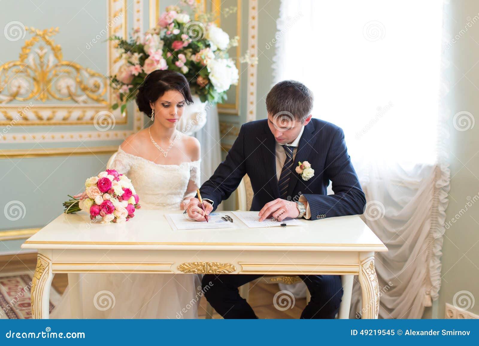 Jong paar die huwelijkscontract ondertekenen