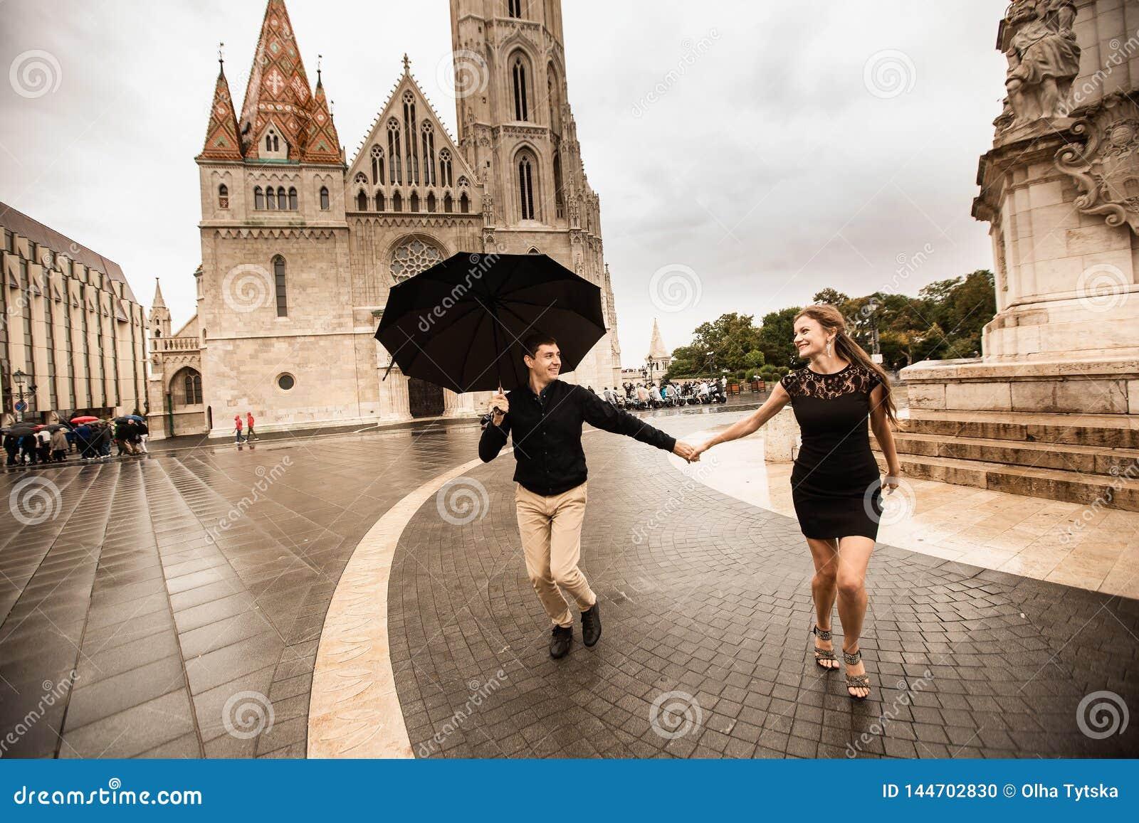 Jong paar die met paraplu in Boedapest op een regenachtige dag lopen Het verhaal van de liefde