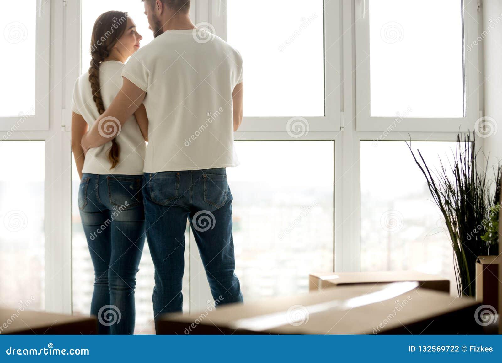 Jong paar die in nieuwe flat met ingepakte bezittingen omhelzen