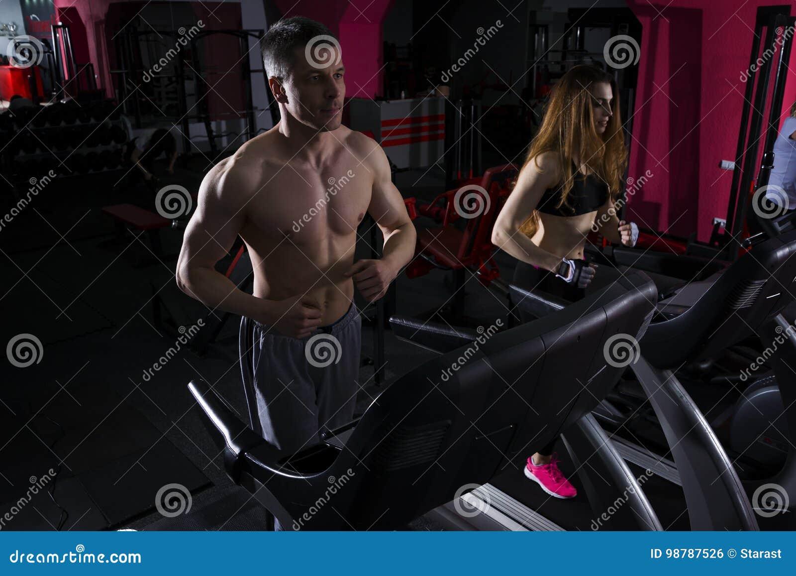 Jong paar die op tredmolen in de gymnastiek lopen
