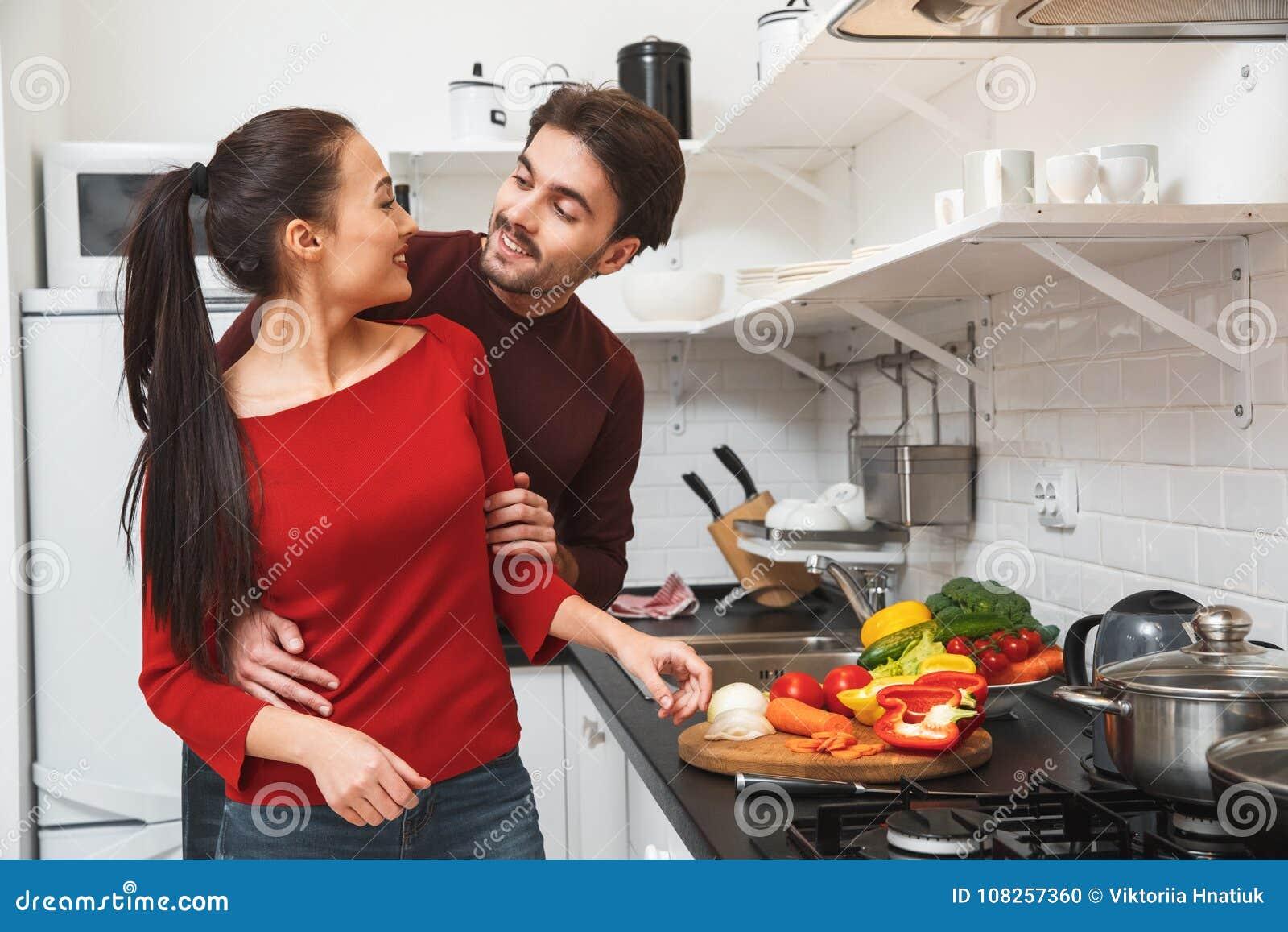 Jong paar die romantische avond thuis in de keuken hebben die samen het koesteren koken