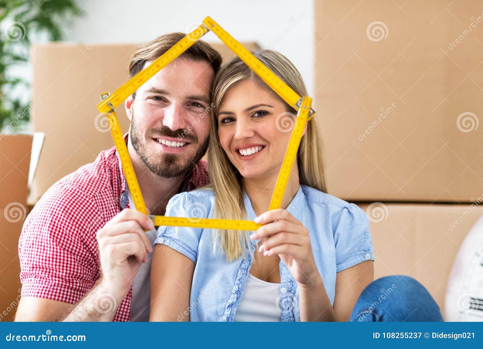 Jong paar die zich aan nieuw huis bewegen, die huis houden samen en smil