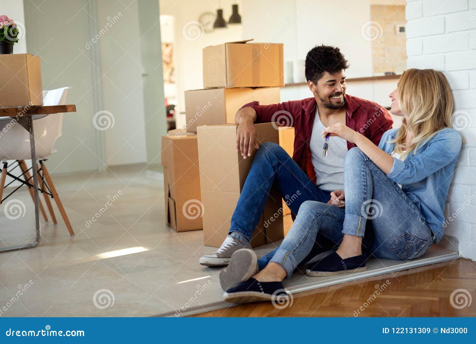 Jong paar die zich in nieuw huis en uitpakkende carboard dozen bewegen