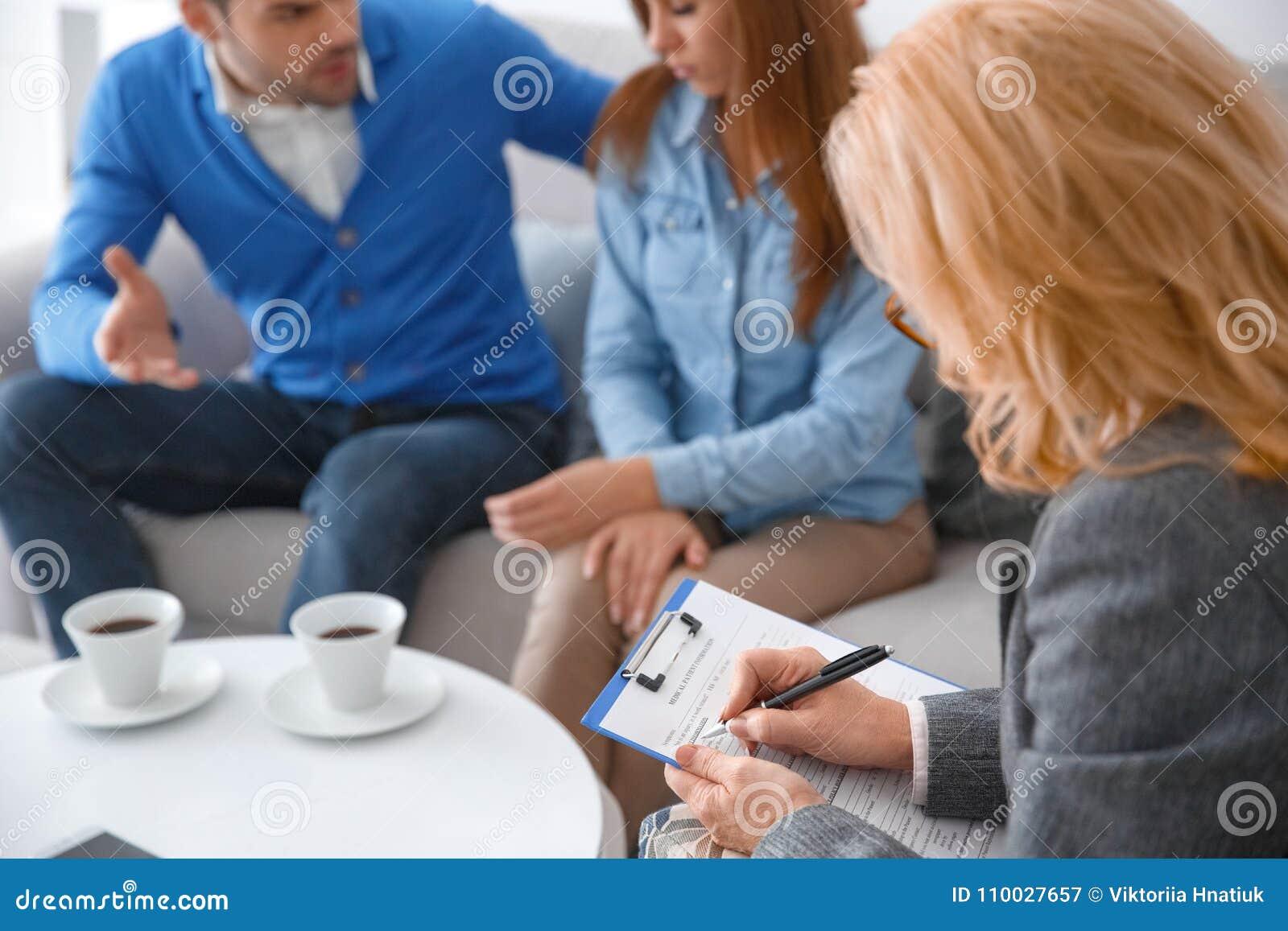 Jong paar met de therapietherapeut die van de psycholoogfamilie medische vorm schrijven