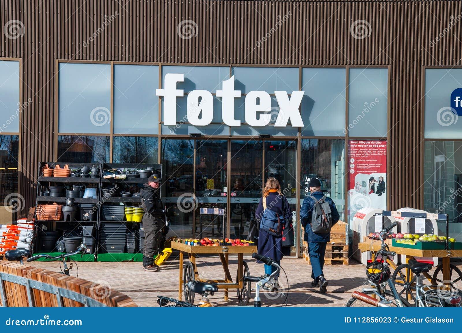 Jong paar naar een supermarkt lopen en een dakloze persoon die een krant verkopen