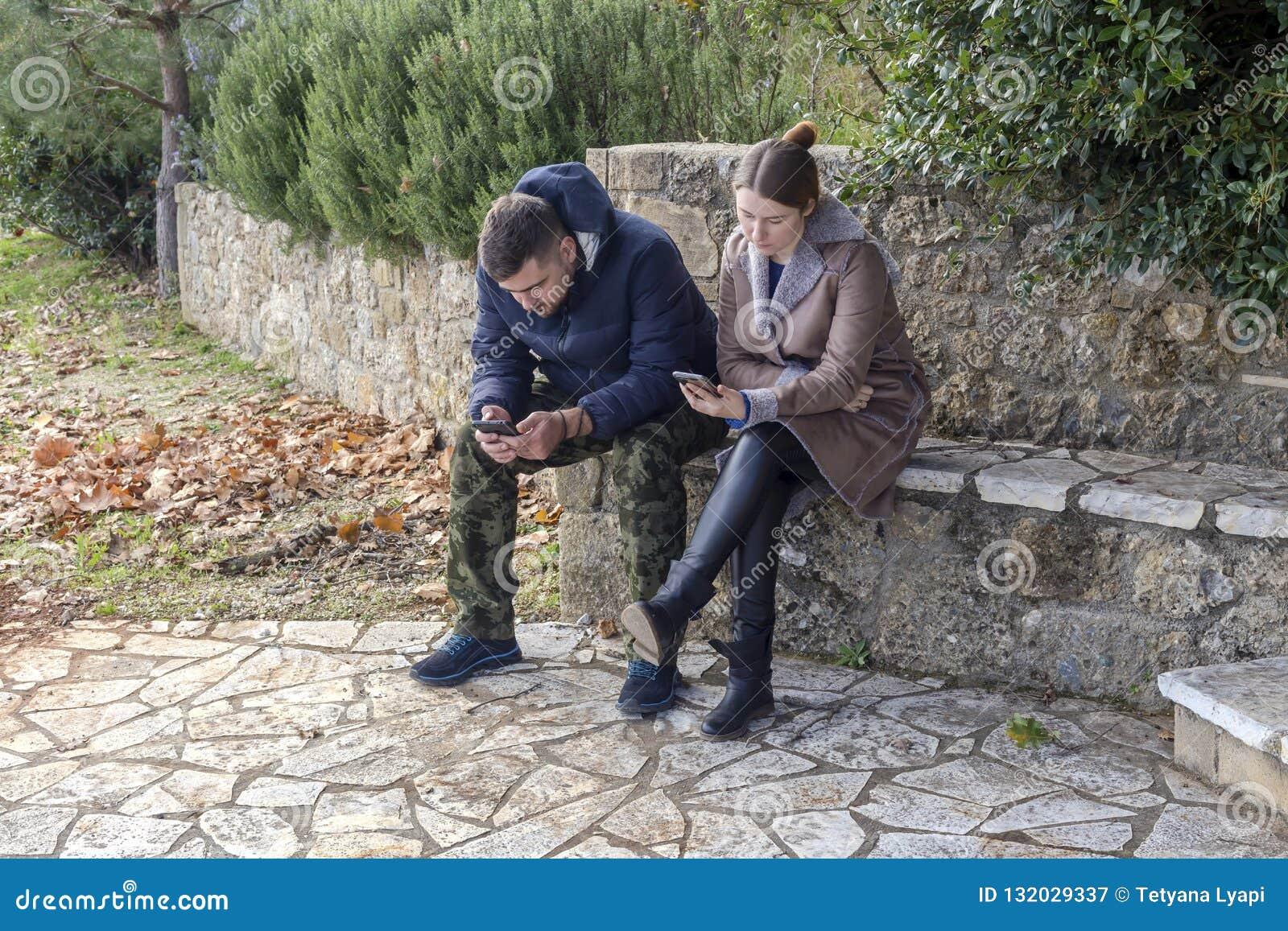 Jong paar op het park met telefoons