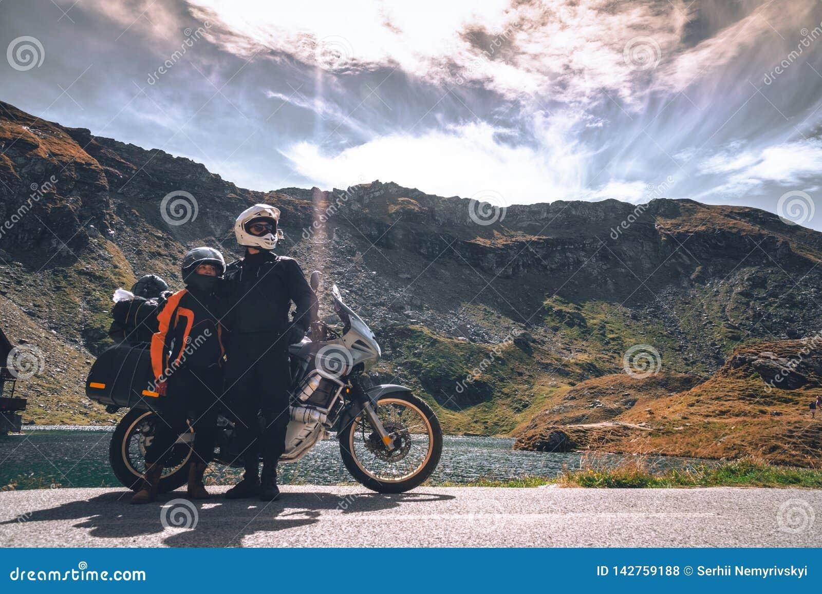 Jong paar van motorfietsreizigers in de de herfstbergen van Roemenië Mototoerisme en motoreizigerslevensstijl terwijl