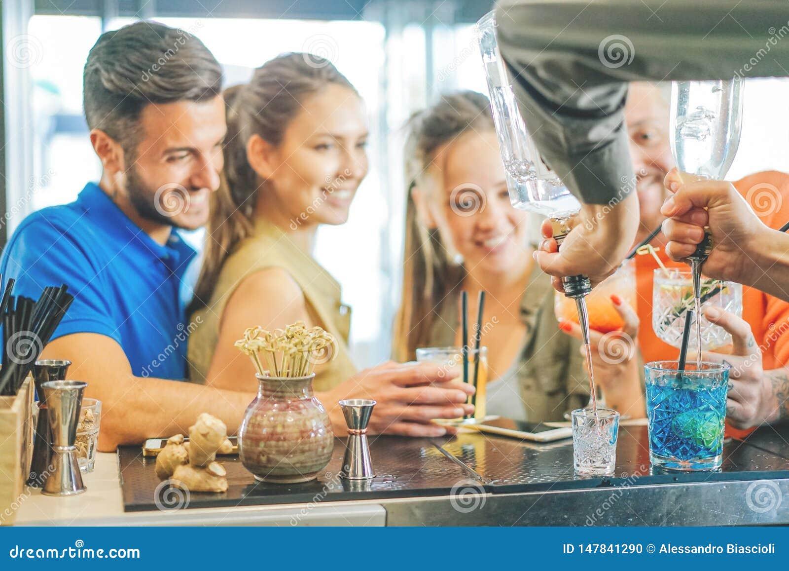 Jong paar van vrienden die cocktails drinken bij de barteller - Barman die kleurrijke cocktail voorbereiden