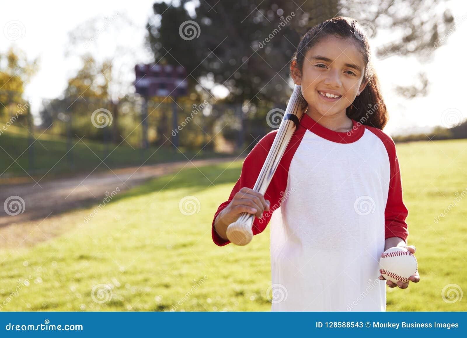 Jong Spaans meisje met honkbal en knuppel die aan camera glimlachen