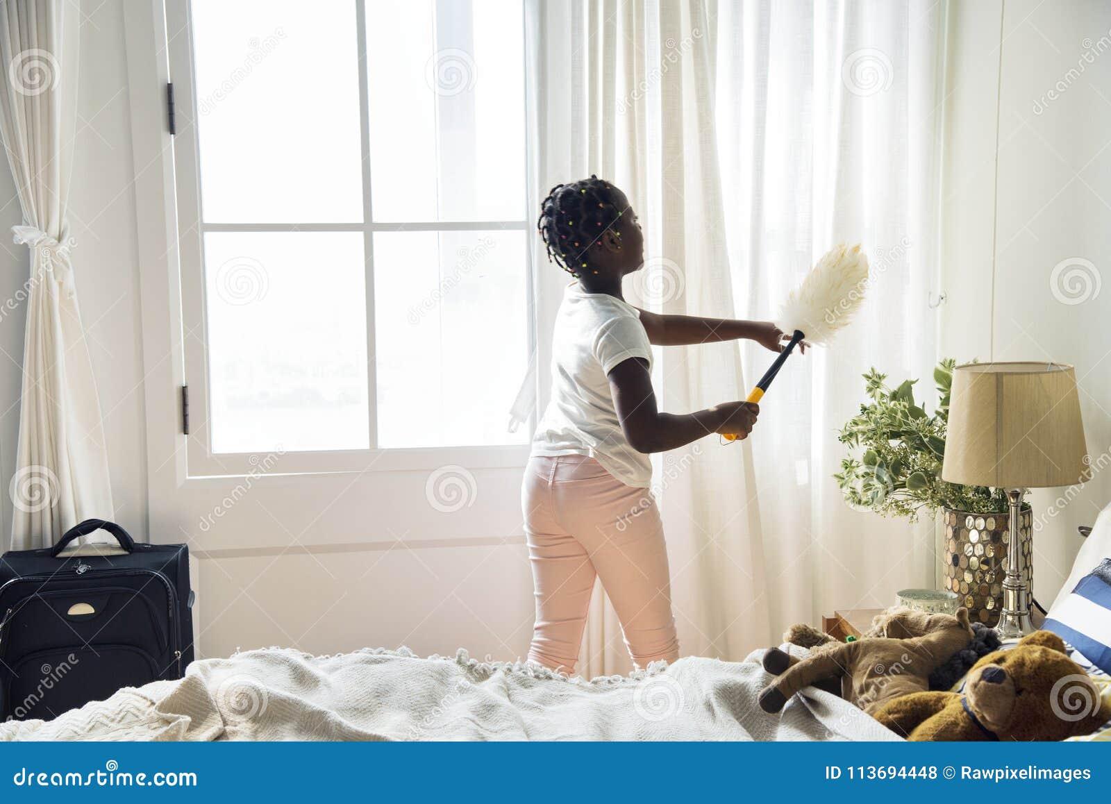 Jong tienermeisje die de slaapkamer schoonmaken stock foto