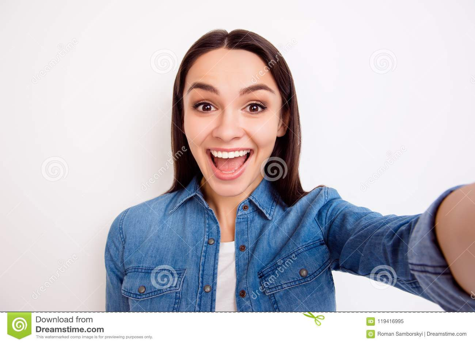 Jong vrij vrolijk meisje in jeansoverhemd die zelf-portret nemen