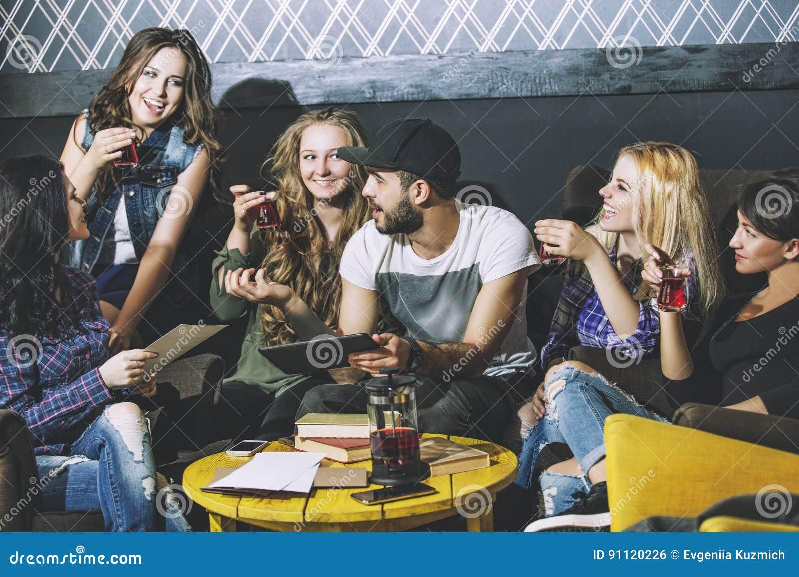 Jong vrolijk bedrijf van vrienden met mede mobiel, tablet en thee