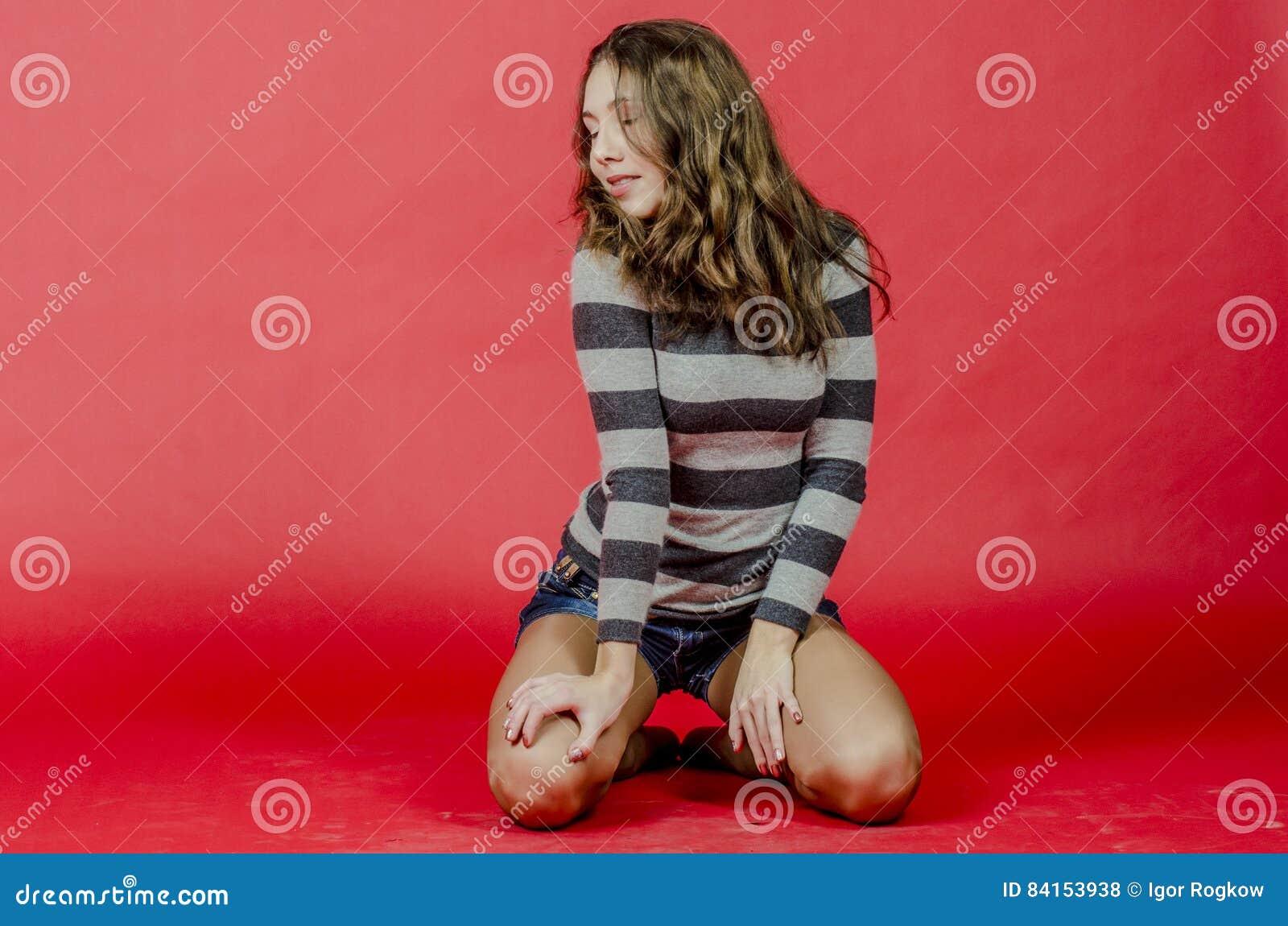 Jong vrolijk meisje in denimborrels en een gestreepte sweater die in de jeugdige stijl lopen