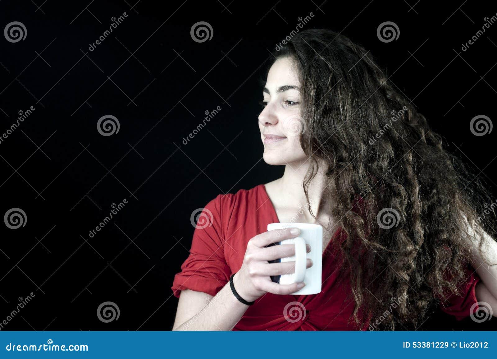 Jong wijfje dat een koffiekop houdt