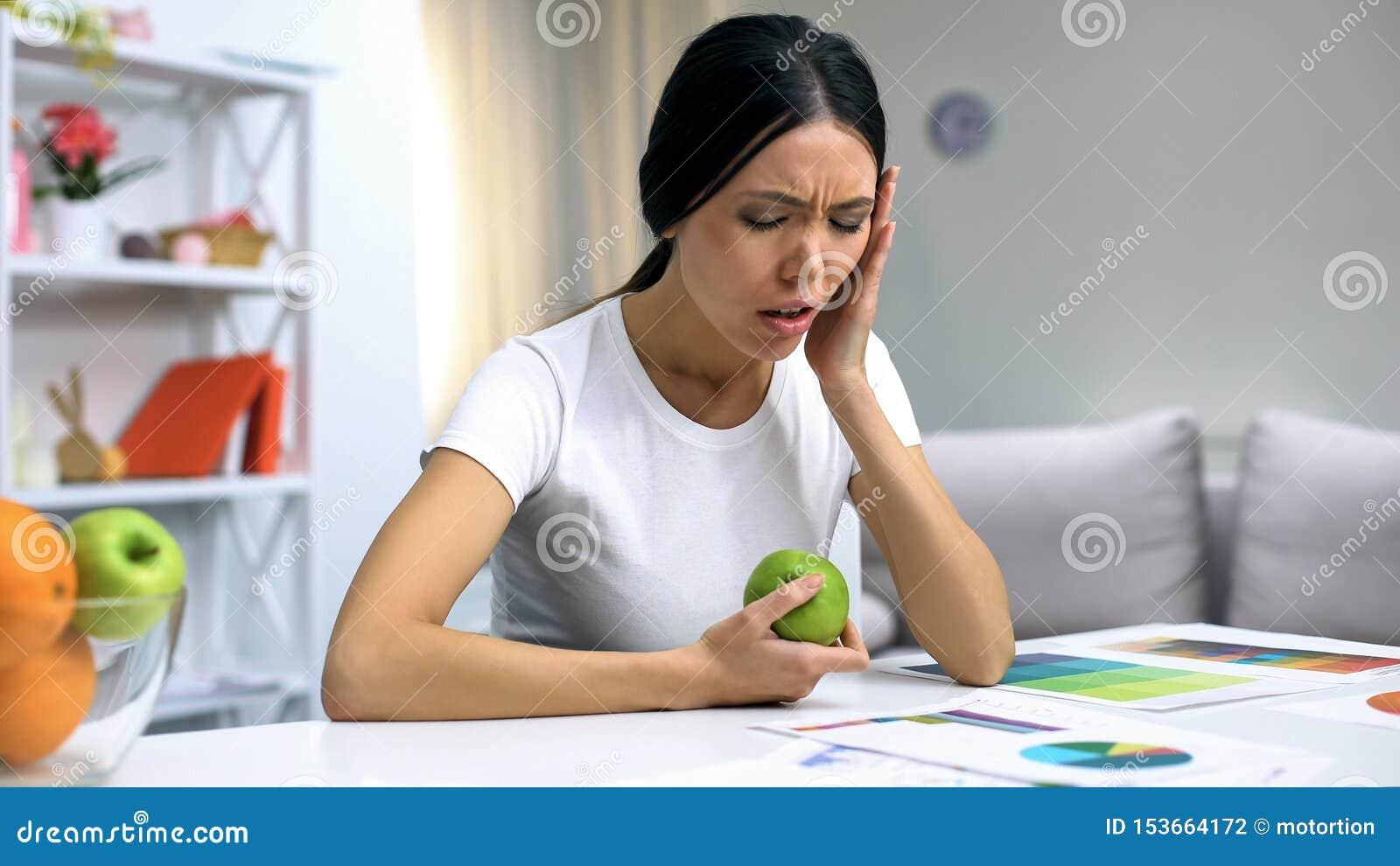 Jong wijfje die freelancer aan tandpijn lijden die groene appel, ontsteking houden