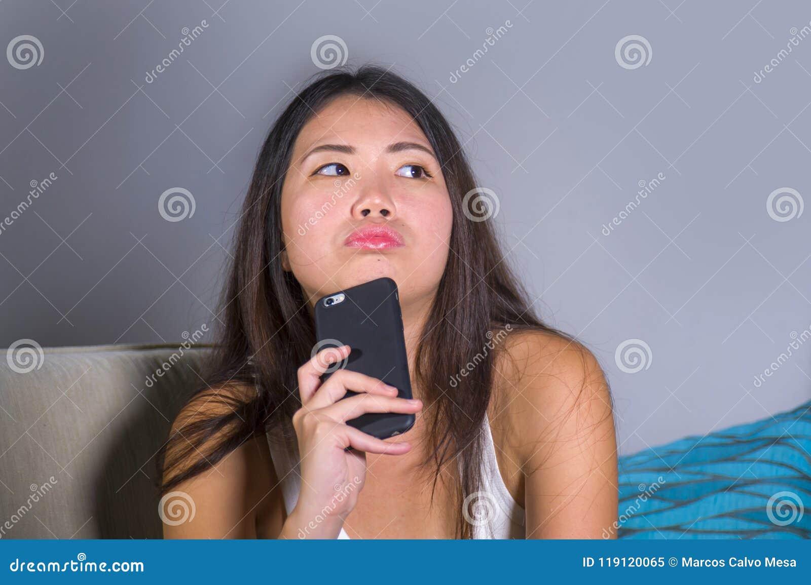 Jong zoet gelukkig en vrij Aziatisch Koreaans meisje die de sociale media app van Internet op mobiele telefoon gebruiken die nade