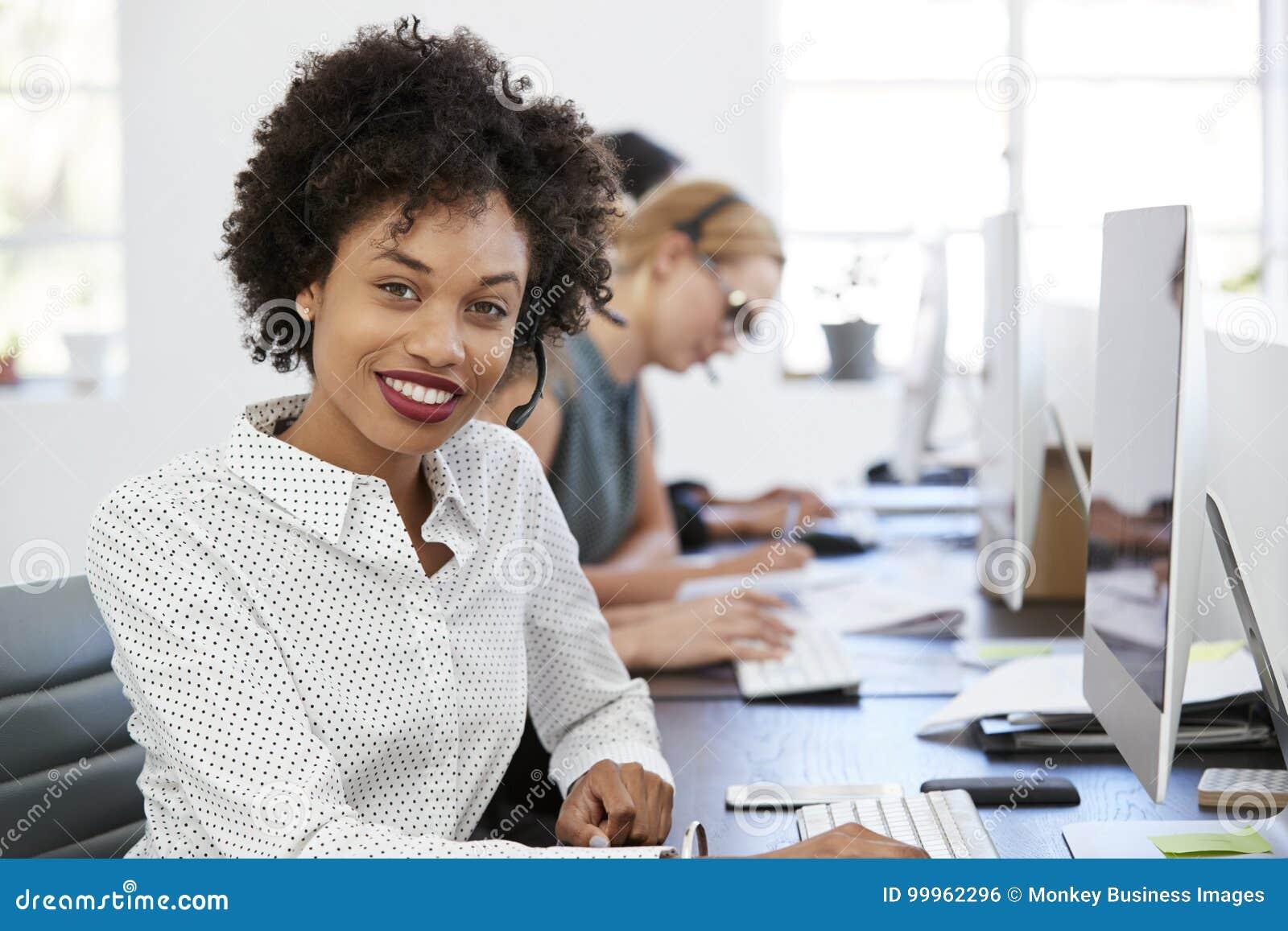 Jong zwarte die met hoofdtelefoon aan camera in bureau glimlachen