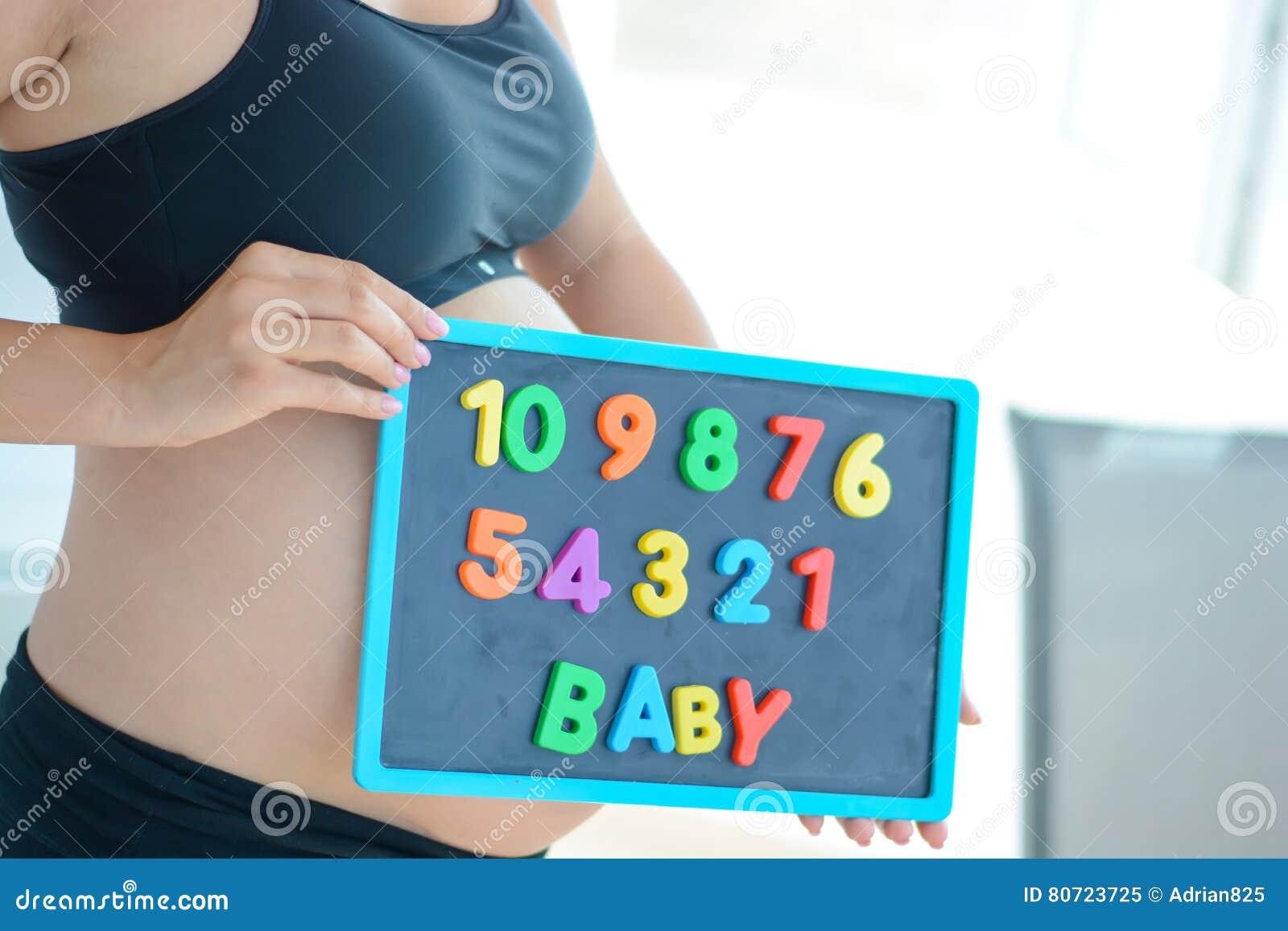 Jonge aanstaande moeder die met brievenblokken baby op magnetisch bord spellen