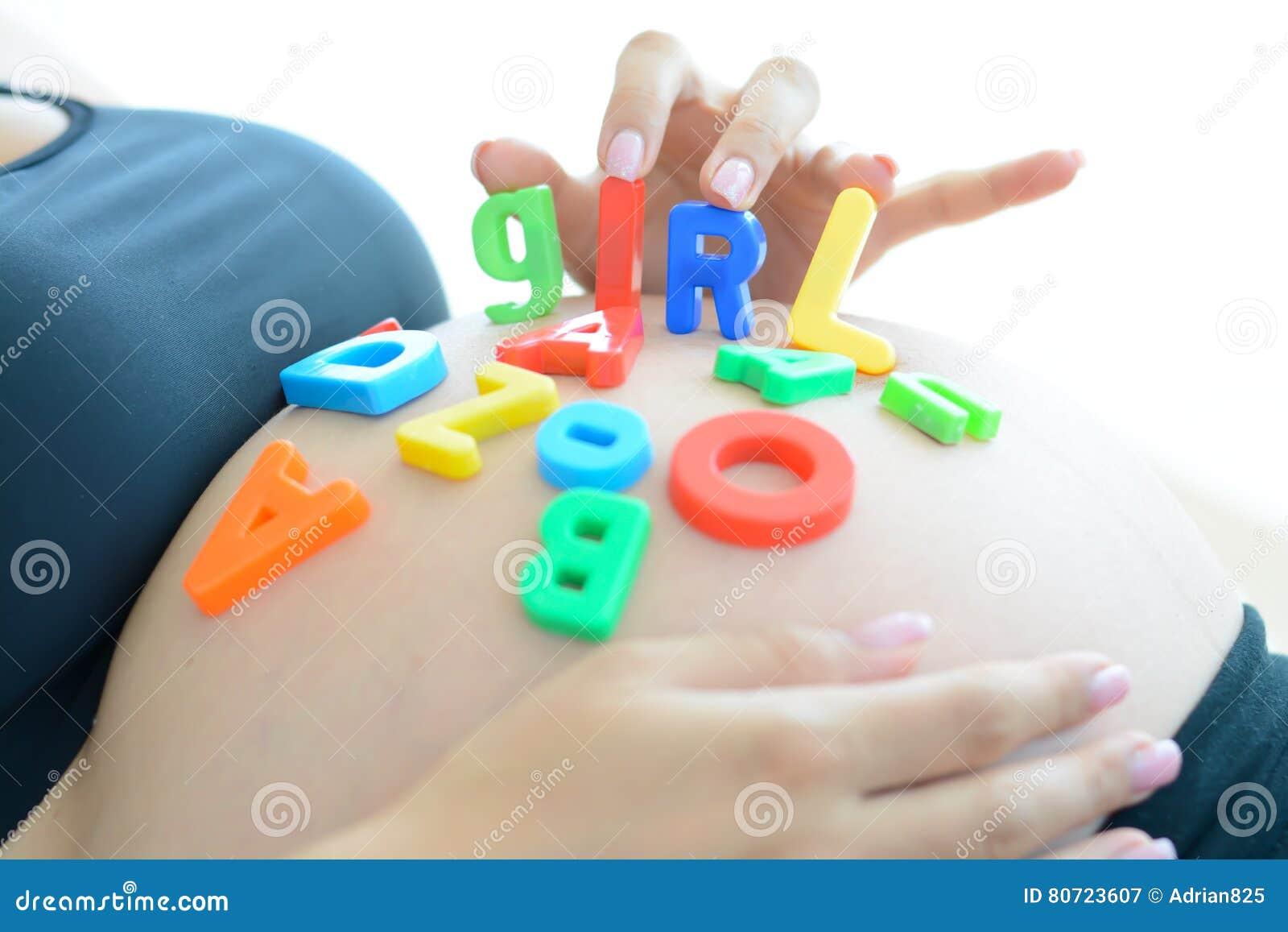 Jonge aanstaande moeder die met brievenblokken meisje op haar zwangere buik spellen