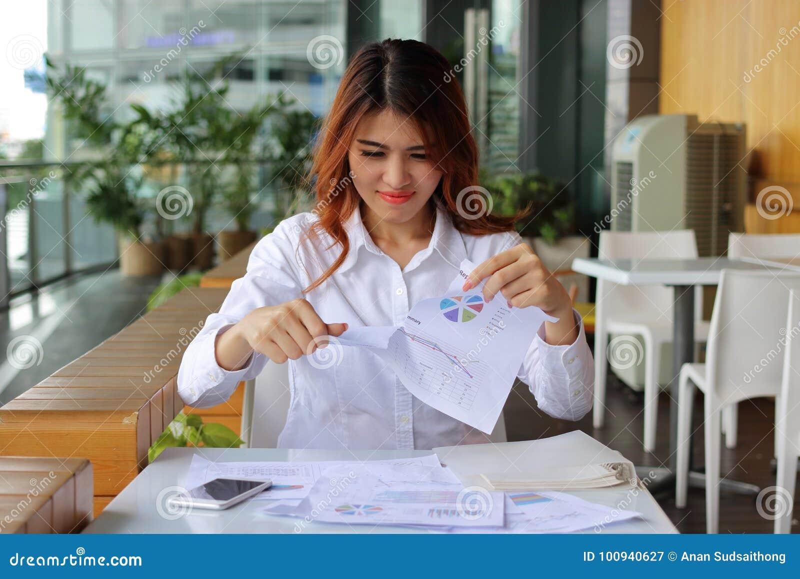 Jonge aantrekkelijke Aziatische bedrijfsvrouwen tearing administratie of grafieken op haar bureauachtergrond