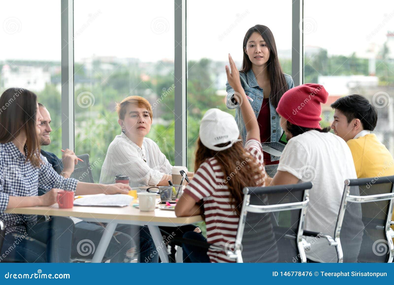Jonge aantrekkelijke Aziatische creatieve hipster vrouwelijke leider die zich bij moderne van de bureau gelukkige het spreken en