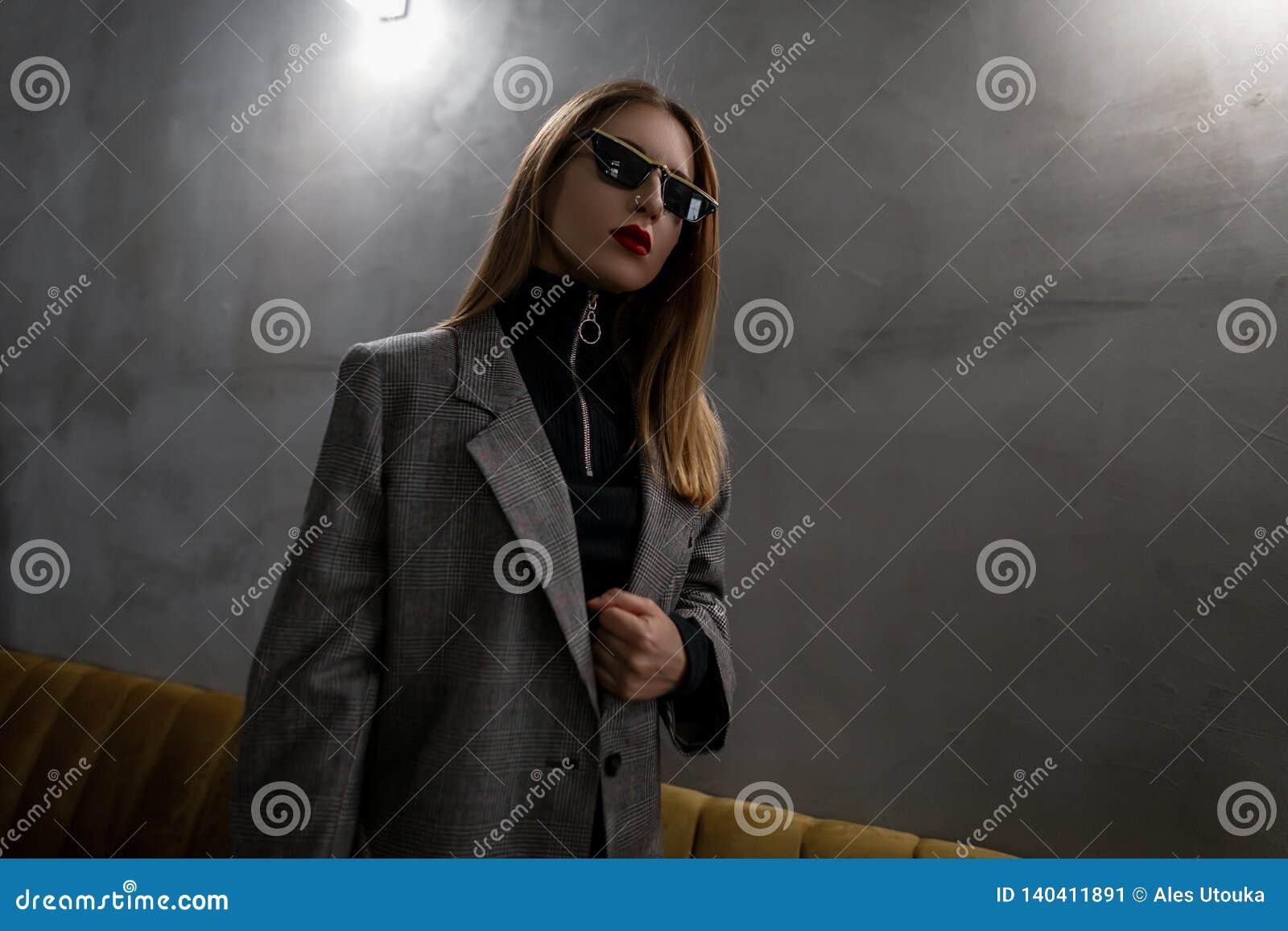 Jonge aantrekkelijke hipstervrouw in ongebruikelijke modieuze glazen in een uitstekend elegant geruit jasje in een zwart modieus