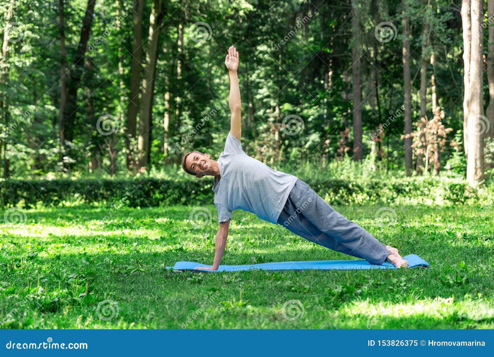 Jonge aantrekkelijke mens die yoga in het park doen: houdingsplank