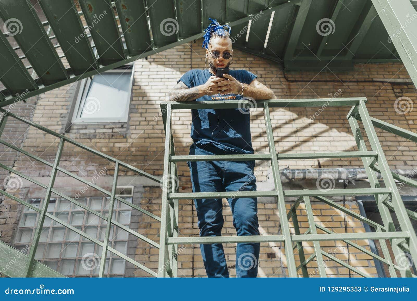 Jonge aantrekkelijke mens met blauwe dreadlocks die zich bij trap bevinden