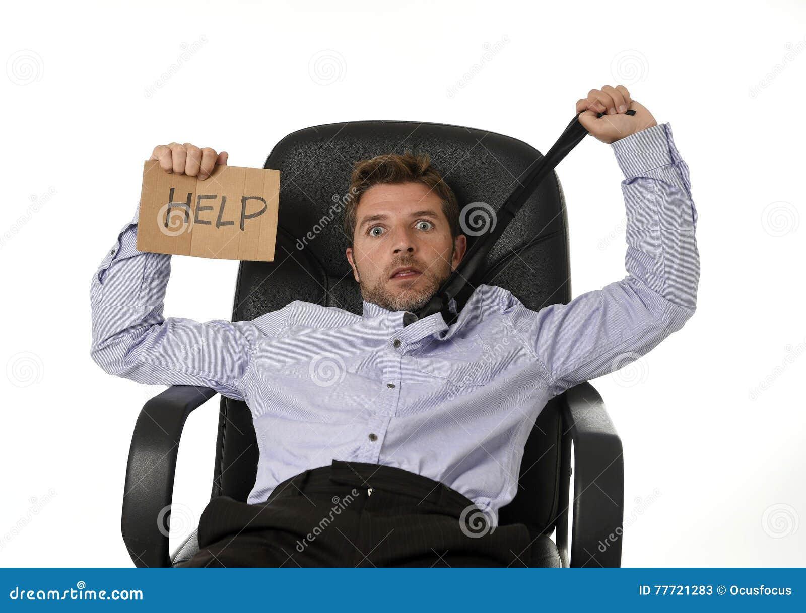 Jonge aantrekkelijke vermoeide en verspilde zakenmanzitting op bureaustoel die om hulp in spanning vragen