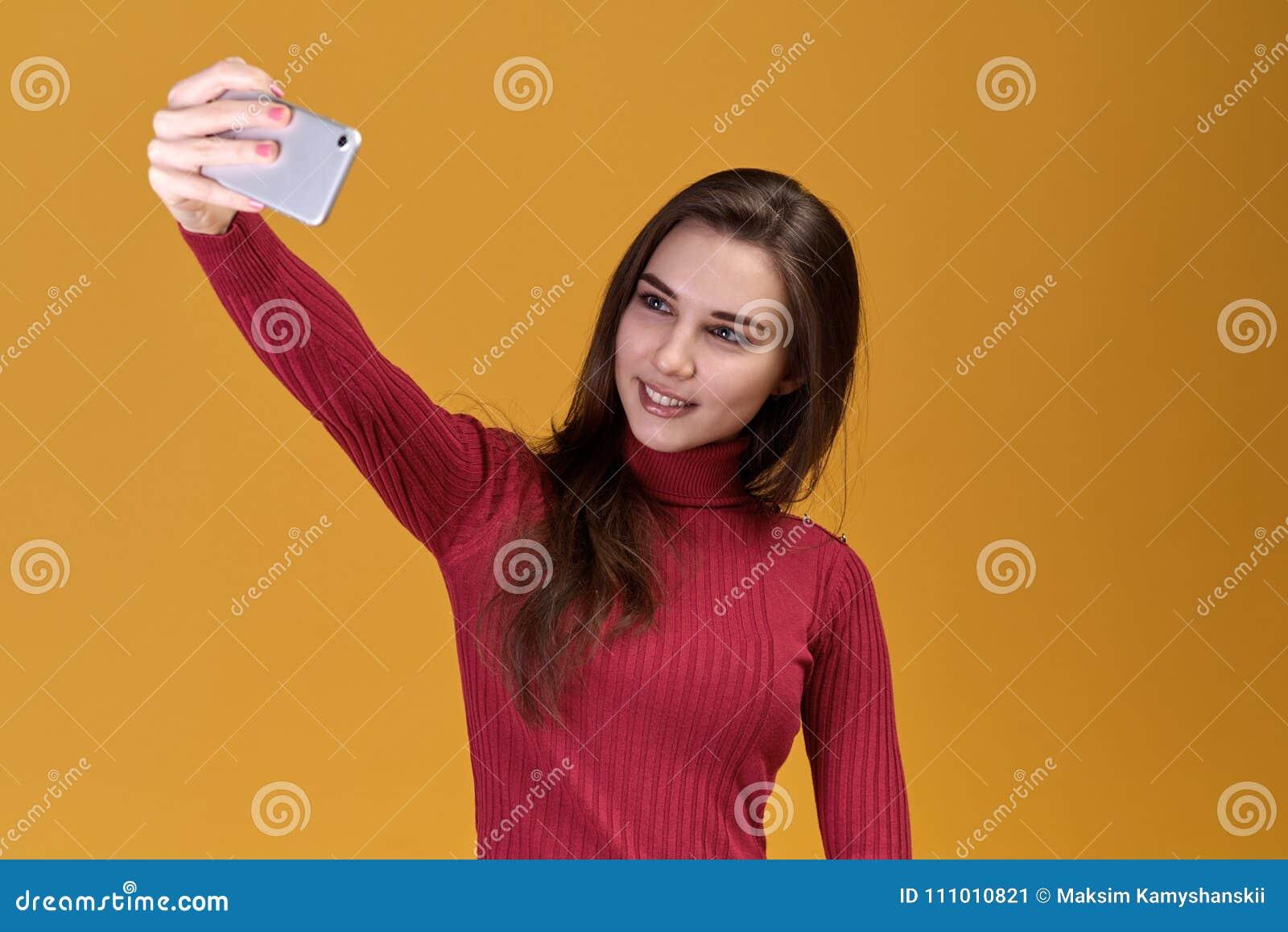 Jonge aantrekkelijke vrouw die foto op geheugen op geïsoleerde achtergrond nemen Een mooi leuk meisje