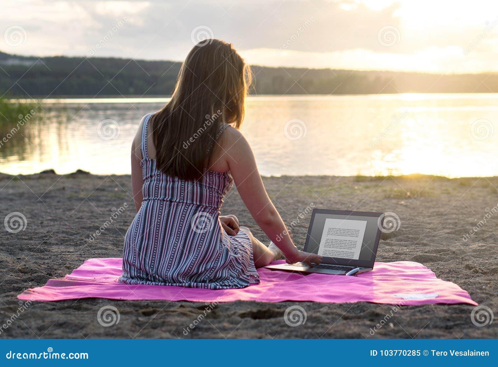 Jonge aantrekkelijke vrouw die laptop op strand met behulp van bij zonsondergang