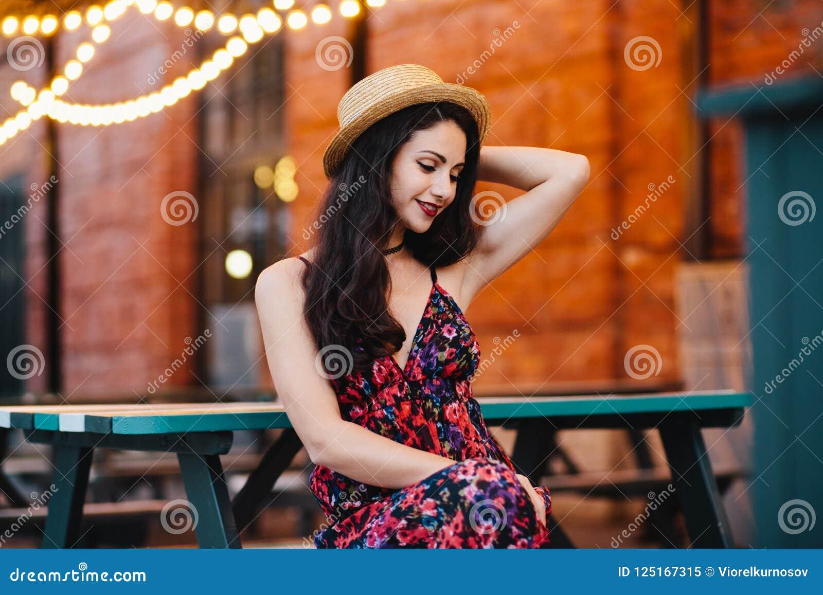 Jonge aantrekkelijke vrouw met Europese verschijningszitting bij bank in openluchtkoffie, die hoed en kleding dragen, die haar ha
