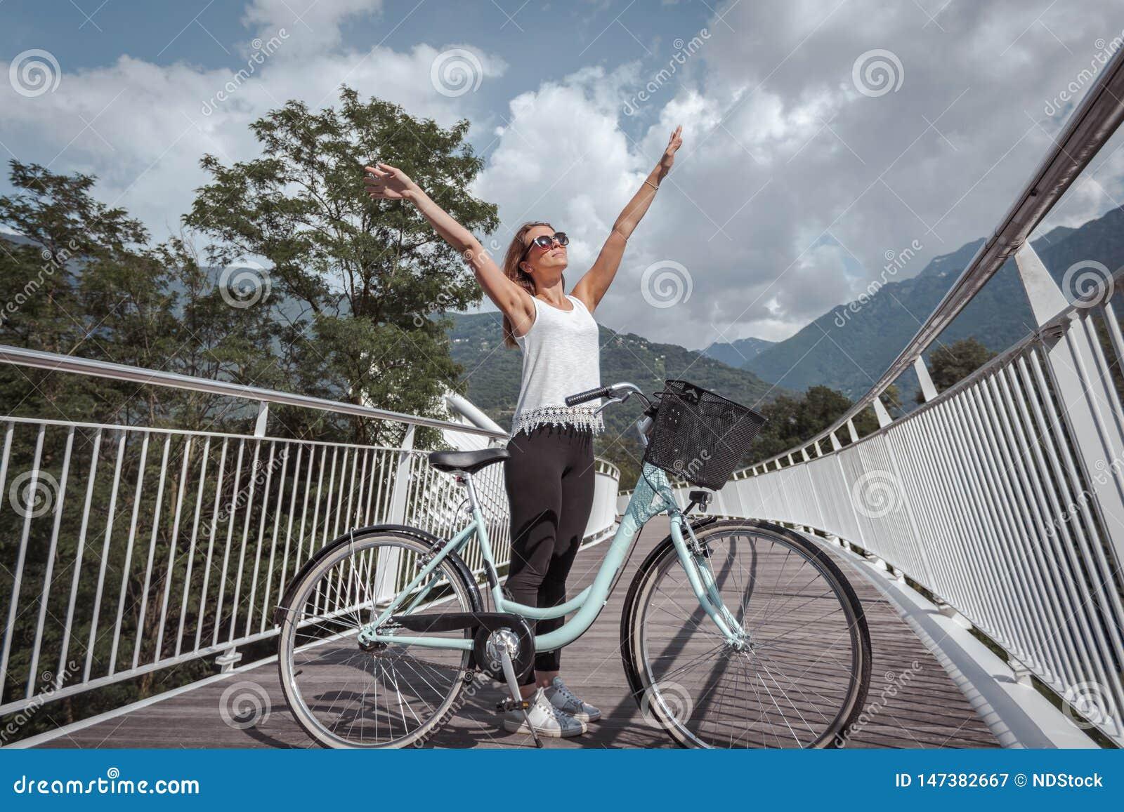 Jonge aantrekkelijke vrouw met fiets op een brug