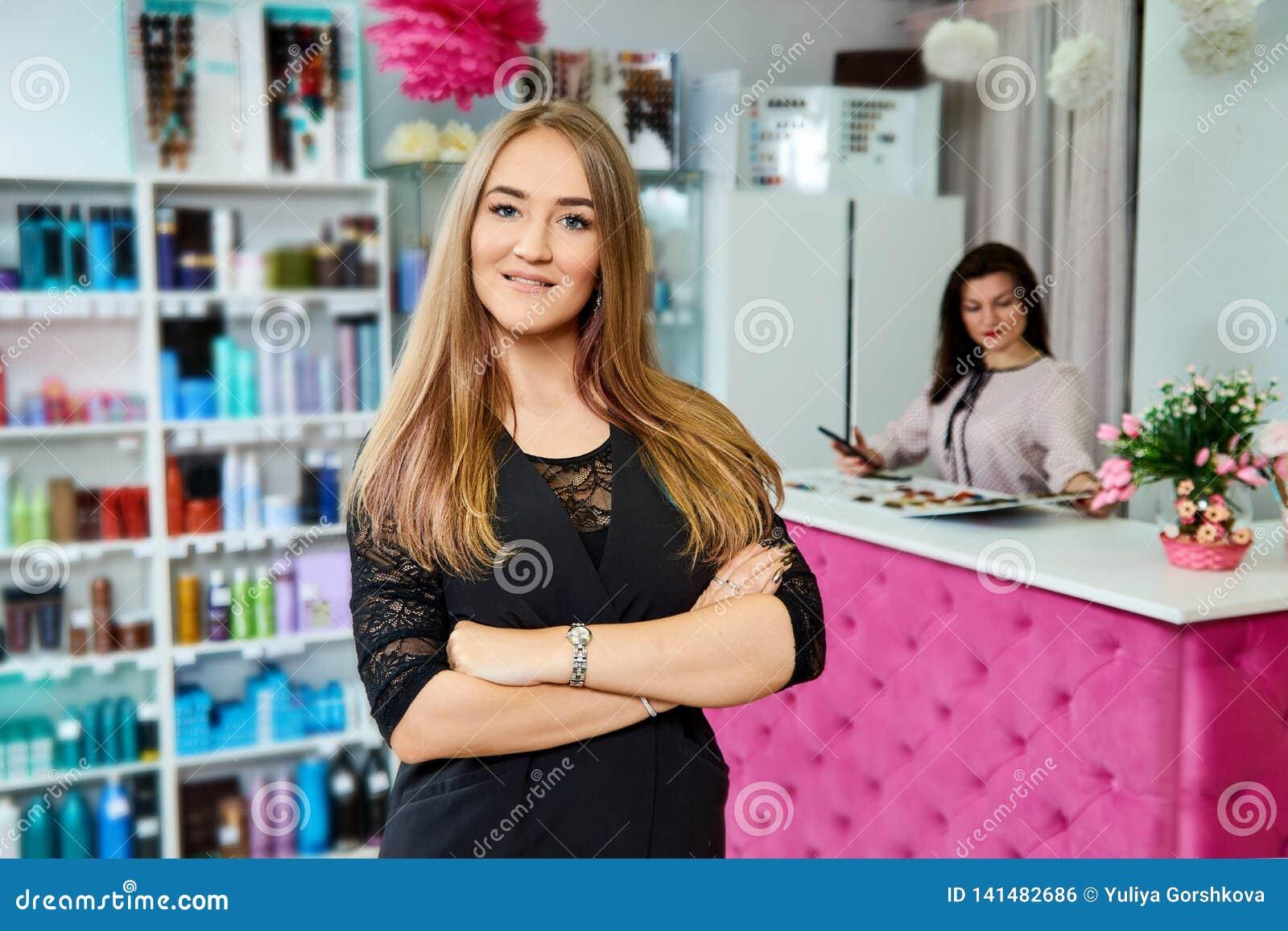 Jonge aantrekkelijke vrouwelijke receptionnist die van schoonheidssalon zich met gekruiste handen bevinden