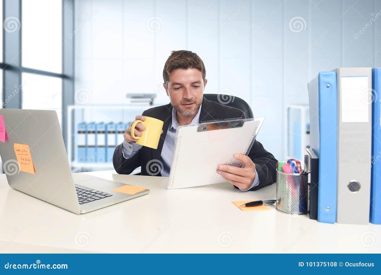 Jonge aantrekkelijke zakenman die gelukkige zeker werken op kantoor met laptop computer en administratie