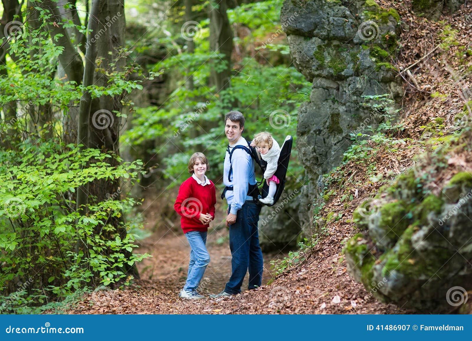 Jonge actieve vader die in klip en bos met jonge geitjes wandelen