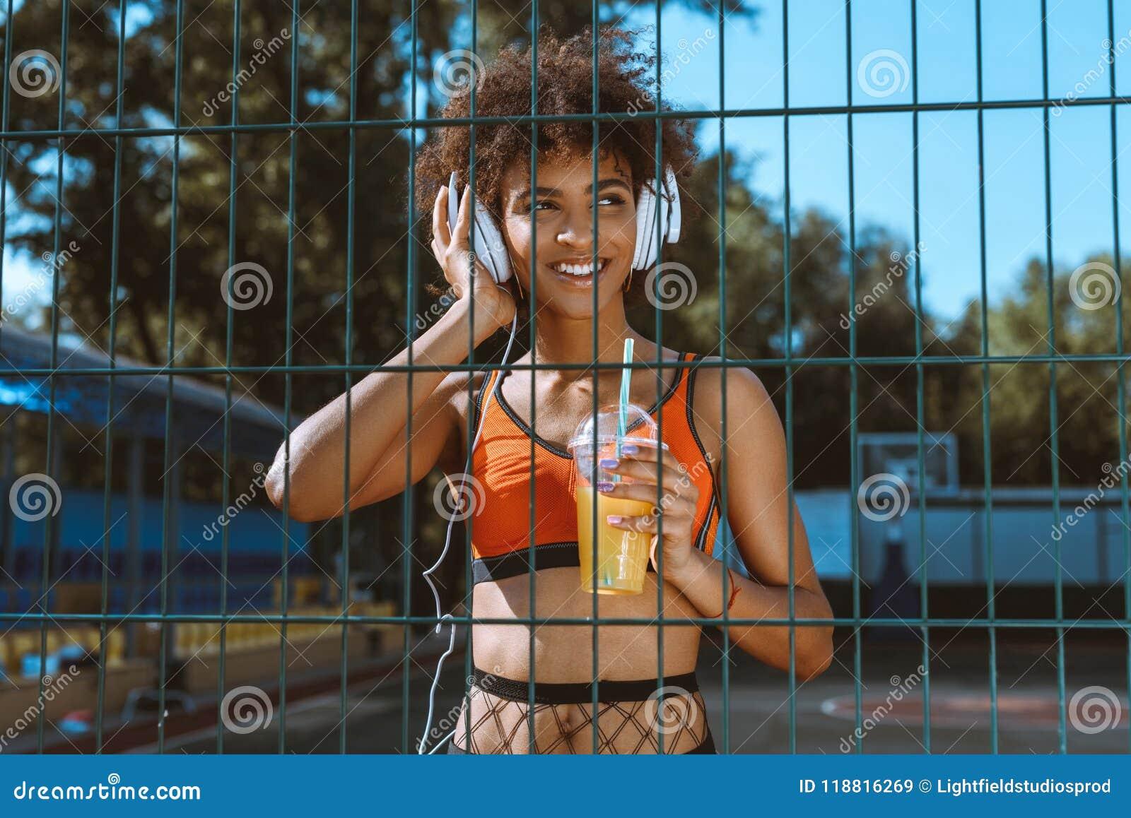 Jonge Afrikaans-Amerikaanse vrouw die in sportkleding aan muziek in hoofdtelefoons en het drinken luisteren