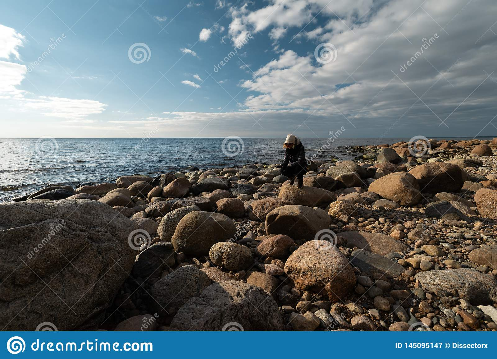 Jonge archeoloog op een keistrand die exotische rotsen op een kustlijn van een Oostzee zoeken
