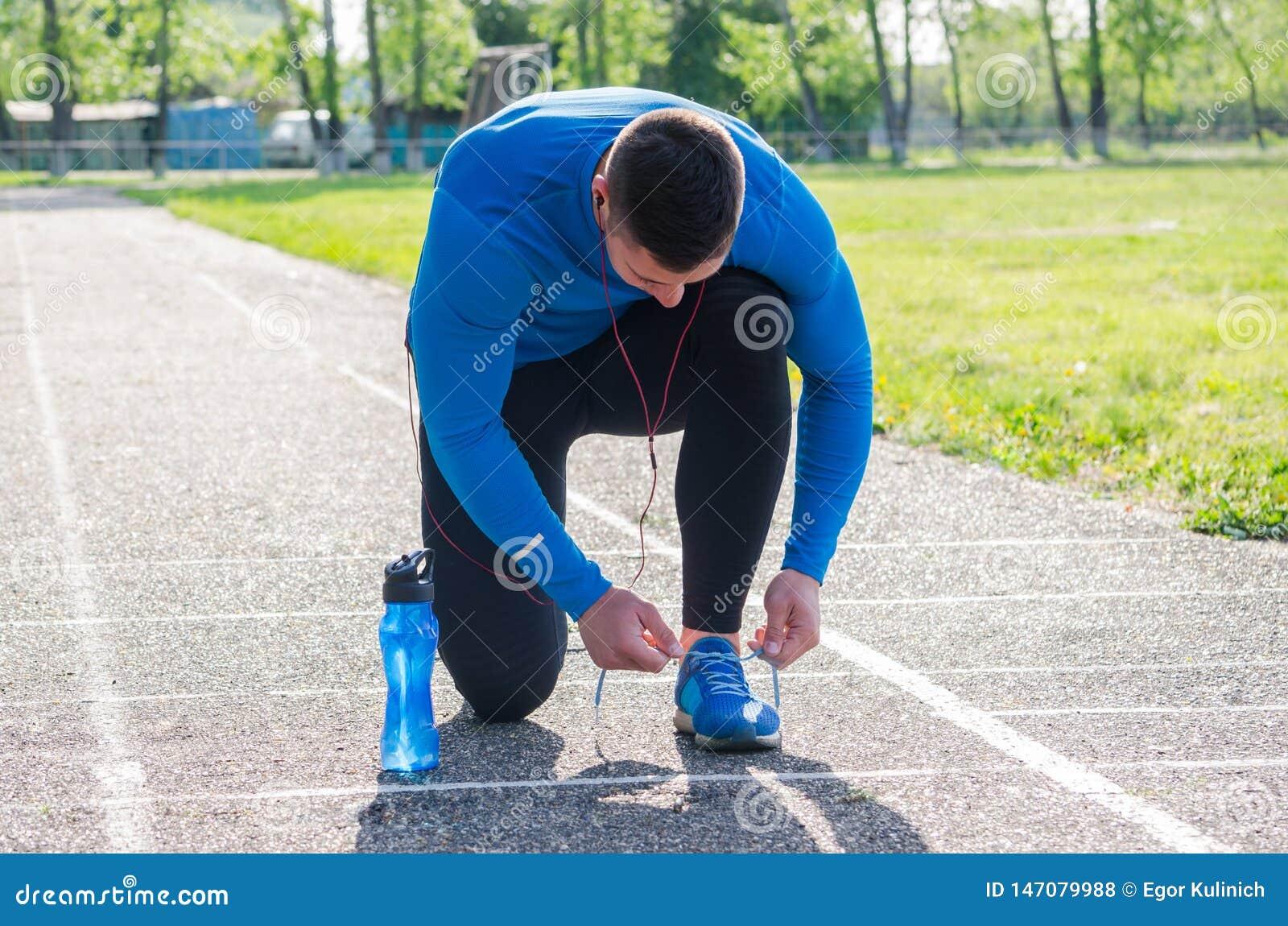 Jonge atleet in hoofdtelefoons, gebonden sportenschoenen