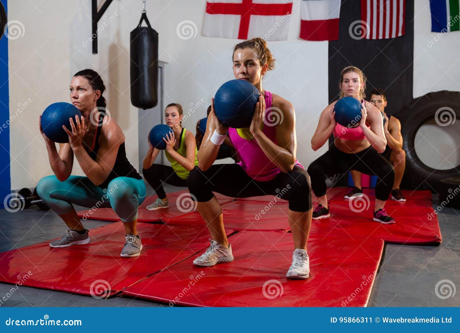 Jonge atleten die met oefeningsballen buigen op matten