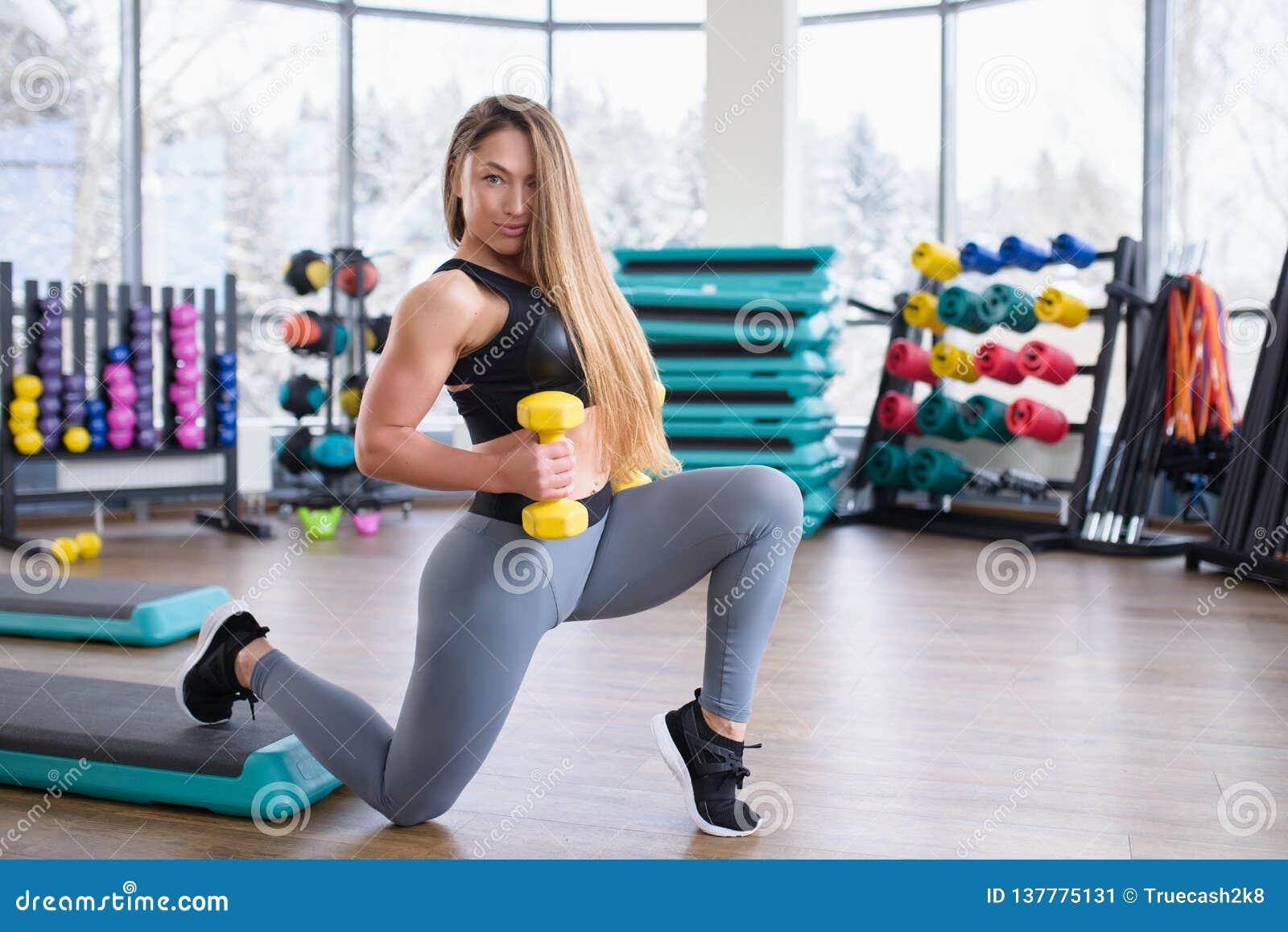 Jonge atletische vrouw opleiding met domoren bij gymnastiek Geschiktheid en gezond levensstijlconcept Mooi Kaukasisch meisje